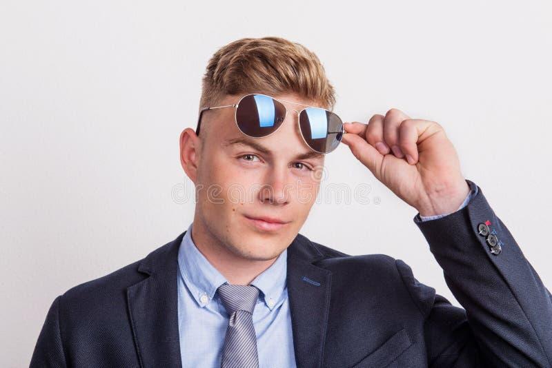 Το πορτρέτο ενός βέβαιου νεαρού άνδρα με τα γυαλιά ηλίου σε ένα στούντιο, φθορά ταιριάζει και δεσμός στοκ εικόνες