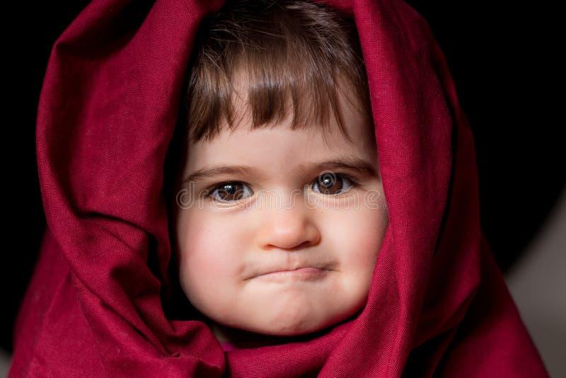 Το πορτρέτο ενός μικρού κοριτσιού έντυσε ως κόκκινη οδηγώντας κουκούλα, με ένα ιδιόμορφο βλέμμα και δάγκωμα του χειλιού στοκ εικόνα