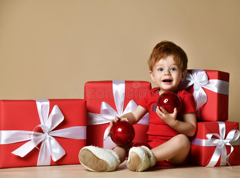 Το πορτρέτο ενός μωρού έντυσε ένα κόκκινο κομπινεζόν με τις κόκκινες διακοσμήσεις σφαιρών στα παρόντα δώρα Χριστουγέννων πέρα από στοκ φωτογραφία