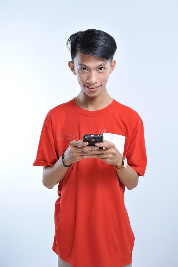 Το πορτρέτο ενός νέου ασιατικού ατόμου σπουδαστών που μιλά στο κινητό τηλέφωνο, μιλά το ευτυχές χαμόγελο στοκ φωτογραφίες