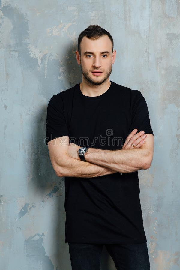 Το πορτρέτο ενός νεαρού άνδρα σε μια μαύρη μπλούζα έκλινε ενάντια σε έναν εκλεκτής ποιότητας γκρίζο τοίχο διάστημα αντιγράφων στοκ εικόνες με δικαίωμα ελεύθερης χρήσης