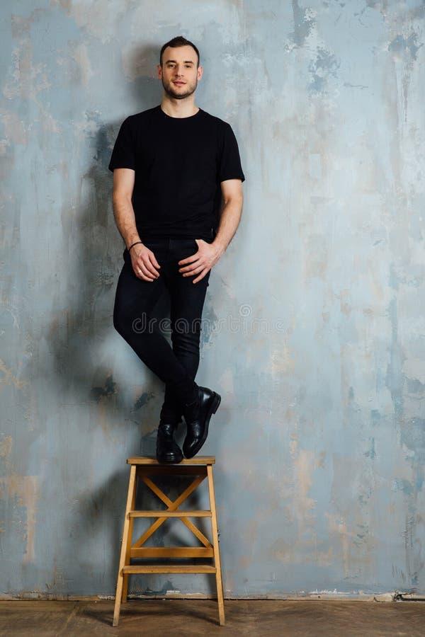 Το πορτρέτο ενός νεαρού άνδρα σε μια μαύρη μπλούζα έκλινε ενάντια σε έναν εκλεκτής ποιότητας γκρίζο τοίχο διάστημα αντιγράφων στοκ εικόνες