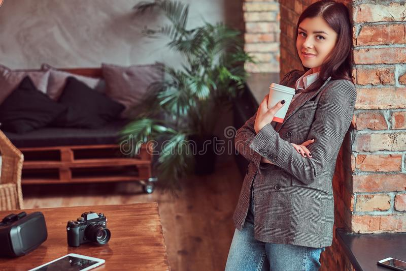 Το πορτρέτο ενός φωτογράφου νέων κοριτσιών έντυσε σε ένα γκρίζο κομψό φλυτζάνι εκμετάλλευσης σακακιών του take-$l*away καφέ κλίνο στοκ εικόνες με δικαίωμα ελεύθερης χρήσης