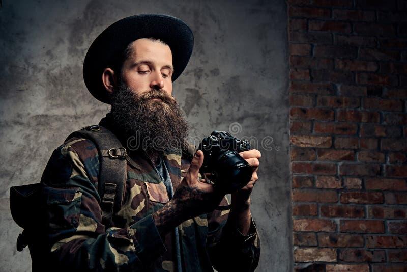 Το πορτρέτο ενός όμορφου γενειοφόρου ταξιδιώτη σε ένα σακάκι καπέλων και κάλυψης, με ένα σακίδιο πλάτης και διαστισμένα όπλα, κρα στοκ εικόνα με δικαίωμα ελεύθερης χρήσης