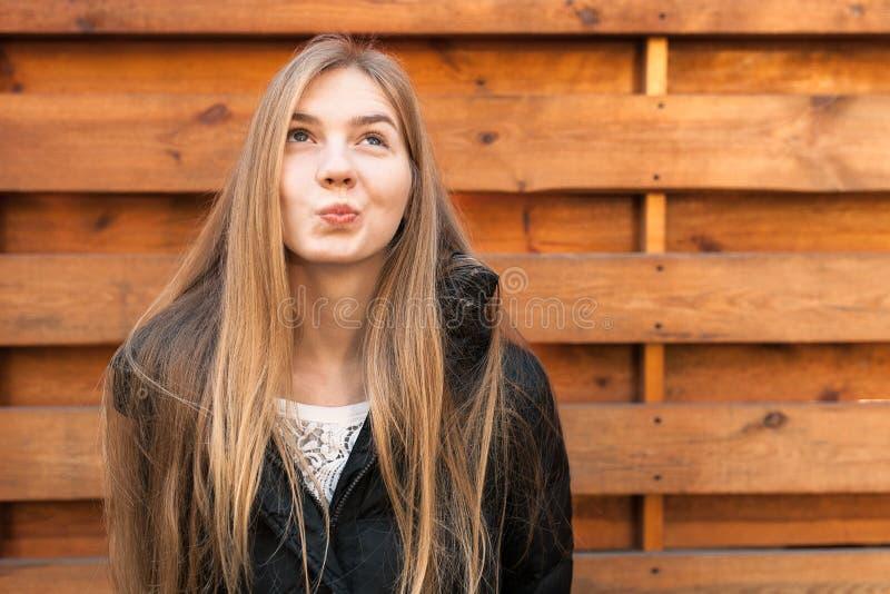 Το πορτρέτο ενός όμορφου κοριτσιού για κάτι ονειρεύεται Στην ξύλινη ανασκόπηση στοκ φωτογραφία με δικαίωμα ελεύθερης χρήσης