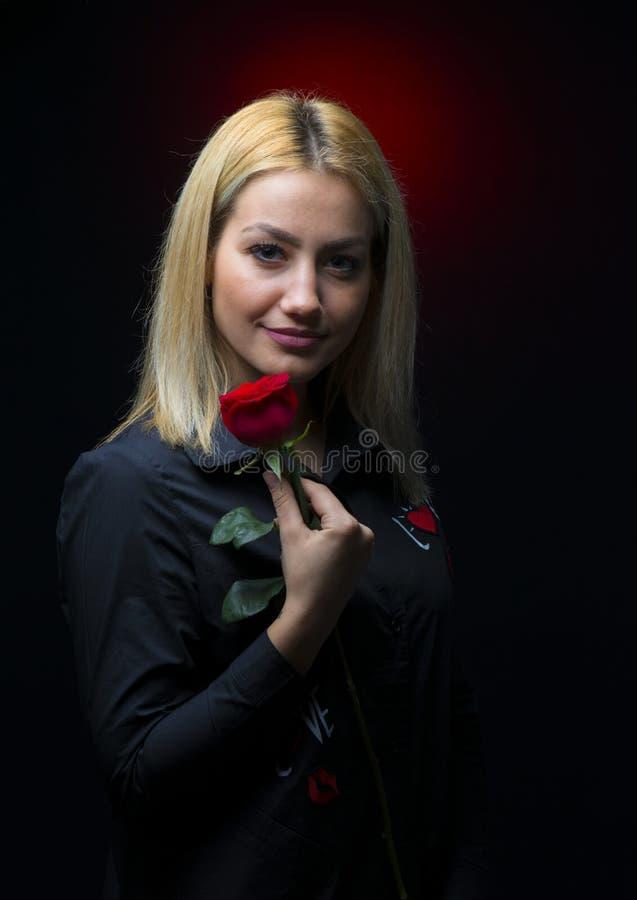 Το πορτρέτο ενός όμορφου ξανθού κοριτσιού με ένα κόκκινο αυξήθηκε στο χέρι της που απομονώθηκε στοκ εικόνες με δικαίωμα ελεύθερης χρήσης