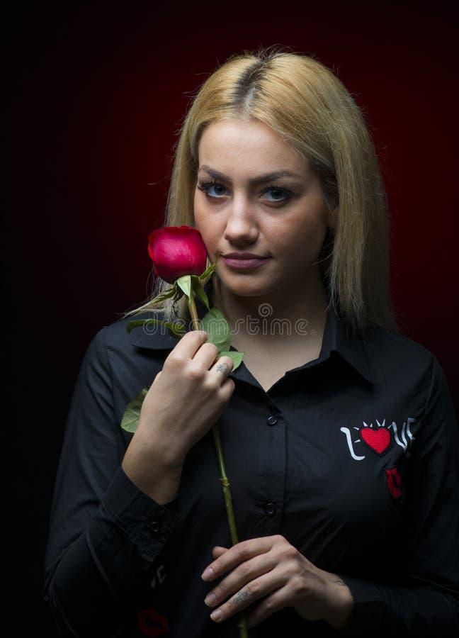 Το πορτρέτο ενός όμορφου ξανθού κοριτσιού με ένα κόκκινο αυξήθηκε στο χέρι της που απομονώθηκε στοκ εικόνα