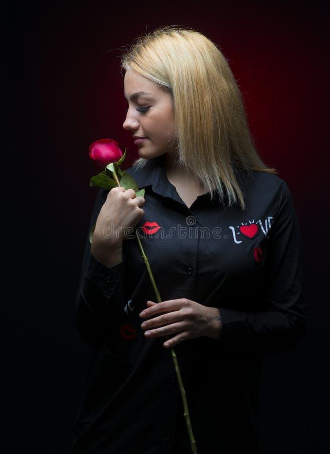 Το πορτρέτο ενός όμορφου ξανθού κοριτσιού με ένα κόκκινο αυξήθηκε στο χέρι της που απομονώθηκε στοκ φωτογραφίες
