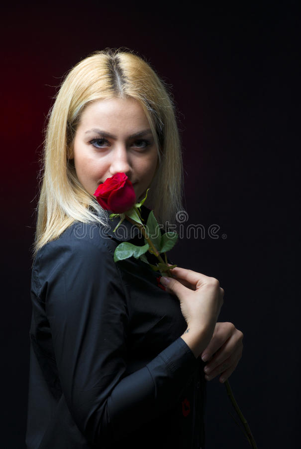 Το πορτρέτο ενός όμορφου ξανθού κοριτσιού με ένα κόκκινο αυξήθηκε στο χέρι της που απομονώθηκε στοκ φωτογραφίες με δικαίωμα ελεύθερης χρήσης