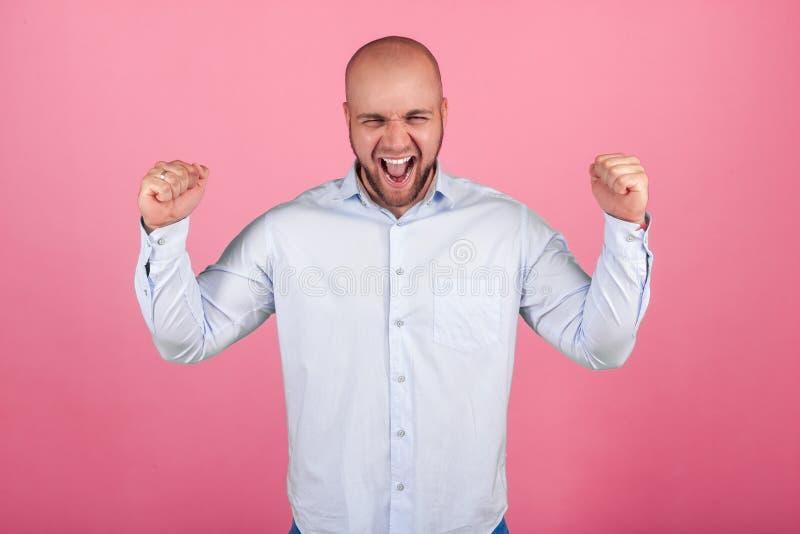 Το πορτρέτο ενός όμορφου φαλακρού ατόμου με μια γενειάδα έντυσε σε ένα άσπρο πουκάμισο κραυγές με τα αυξημένα χέρια κέρδισε τη λα στοκ φωτογραφία