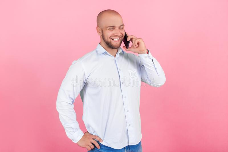Το πορτρέτο ενός όμορφου φαλακρού ατόμου με μια γενειάδα έντυσε σε ένα άσπρο πουκάμισο στάση στο σχεδιάγραμμα και χαμόγελο συζητώ στοκ φωτογραφίες