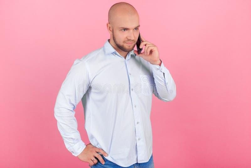 Το πορτρέτο ενός όμορφου φαλακρού ατόμου με μια γενειάδα έντυσε σε ένα άσπρο πουκάμισο στάση σε ένα σχεδιάγραμμα και σοβαρά συζήτ στοκ εικόνα με δικαίωμα ελεύθερης χρήσης