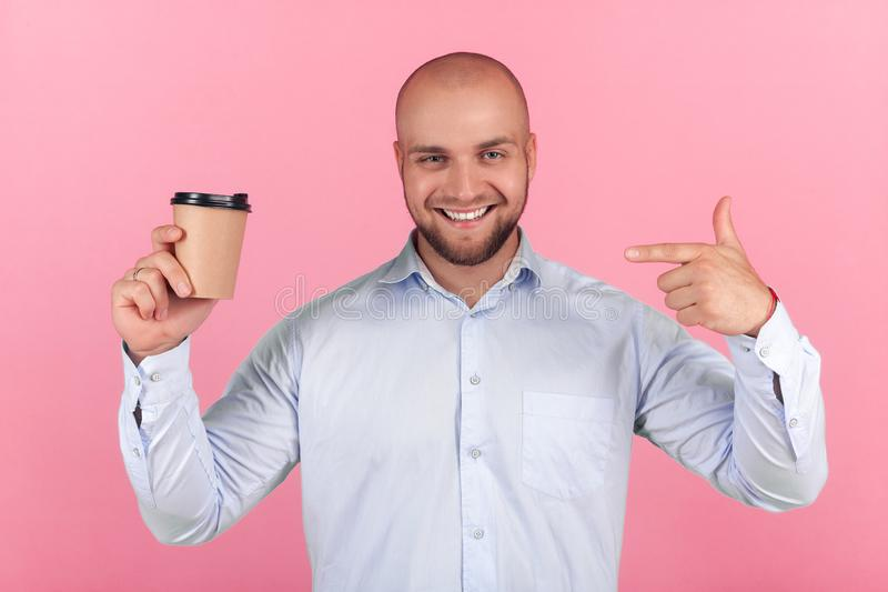 Το πορτρέτο ενός όμορφου φαλακρού ατόμου με μια γενειάδα έντυσε σε ένα άσπρο πουκάμισο σημεία σε ένα φλιτζάνι του καφέ με τις ευτ στοκ φωτογραφίες