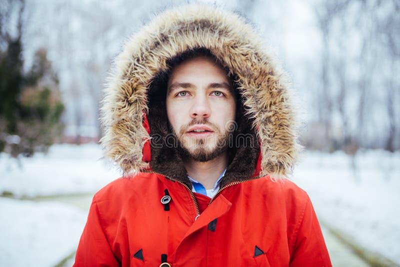 Το πορτρέτο, κινηματογράφηση σε πρώτο πλάνο ενός νέου μοντέρνου ατόμου με μια γενειάδα έντυσε σε ένα κόκκινο χειμερινό σακάκι με  στοκ εικόνα με δικαίωμα ελεύθερης χρήσης