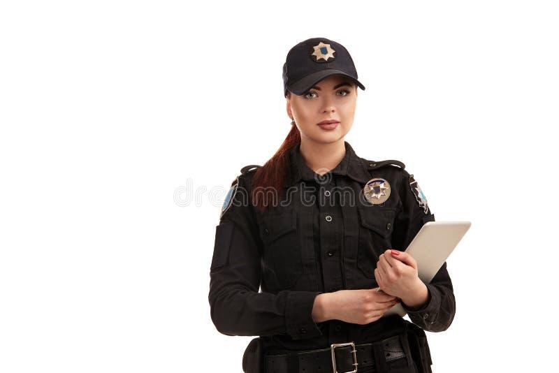 Το πορτρέτο κινηματογραφήσεων σε πρώτο πλάνο μιας γυναίκας αστυνομικός θέτει για τη κάμερα που απομονώνεται στο άσπρο υπόβαθρο στοκ εικόνα
