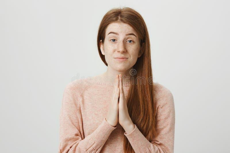 Το πορτρέτο κινηματογραφήσεων σε πρώτο πλάνο του αστείου redhead κοριτσιού με το χαριτωμένο κράτημα φακίδων παραδίδει προσεύχεται στοκ φωτογραφία