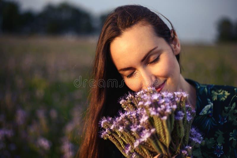 Το πορτρέτο κινηματογραφήσεων σε πρώτο πλάνο του brunette σε ένα floral λιβάδι κρατά για να είναι φρέσκα άγρια λουλούδια ακούοντα στοκ εικόνες