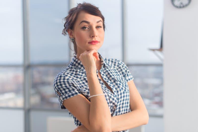 Το πορτρέτο κινηματογραφήσεων σε πρώτο πλάνο μιας κομψής φιλόδοξης νέας γυναίκας, που κρατά τα όπλα διέσχισε, φορώντας το ελεγμέν στοκ φωτογραφία