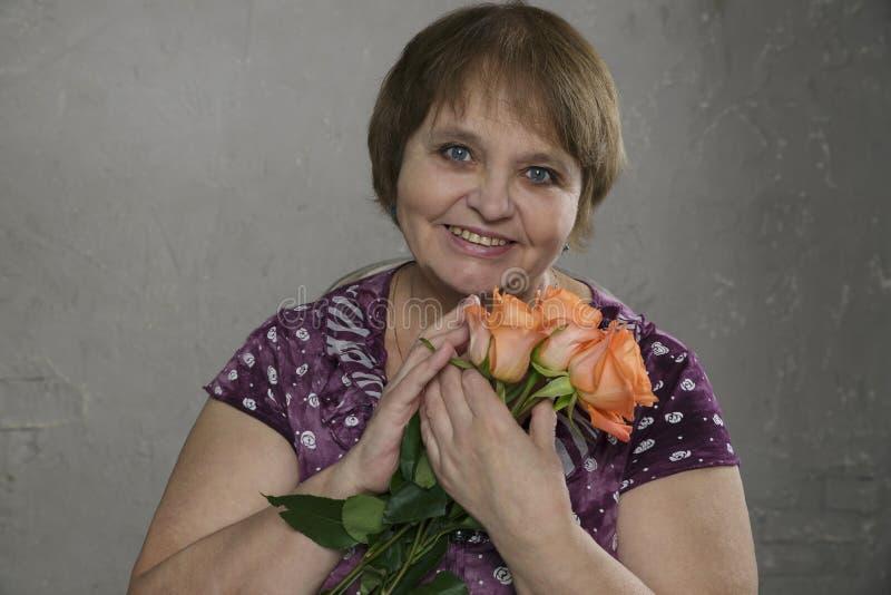 Το πορτρέτο κινηματογραφήσεων σε πρώτο πλάνο της ευτυχούς ηλικιωμένης εκμετάλλευσης γυναικών ανθίζει την εξέταση τη κάμερα και το στοκ φωτογραφίες
