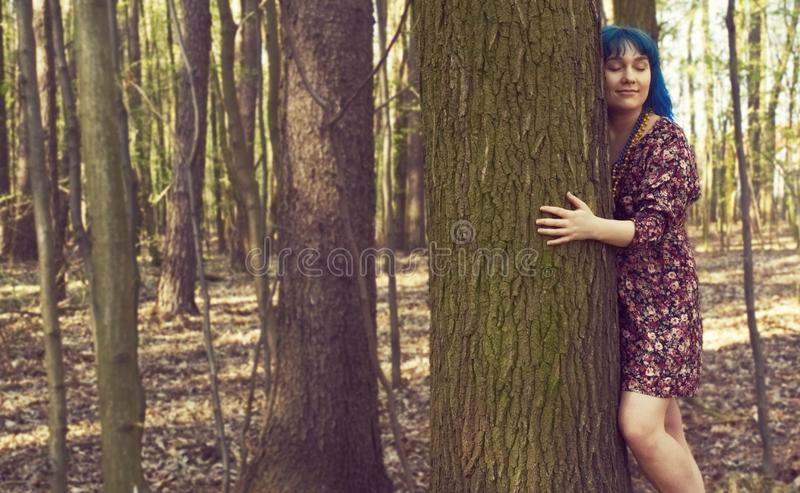 Το πορτρέτο μιας γυναίκας με μια ενδιαφέρουσα εμφάνιση αγκαλιάζει ένα δέντρο στοκ εικόνες