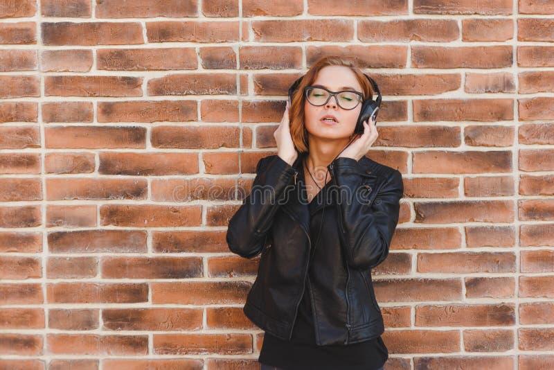 Το πορτρέτο μιας εύθυμης νέας γυναίκας blondhair που απολαμβάνει τη μουσική στα ακουστικά πέρα από το τούβλο grunge περιτοιχίζει  στοκ εικόνα