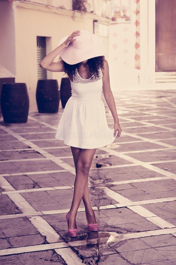 Νέα μαύρη γυναίκα που φορά το καπέλο φορεμάτων και ήλιων, afro hairstyle στοκ εικόνα