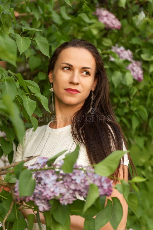Το πορτρέτο μιας νέας ονειροπόλου γυναίκας σε έναν άσπρο τρύγο έπλεξε το φόρεμα στους ιώδεις θάμνους στοκ φωτογραφίες με δικαίωμα ελεύθερης χρήσης