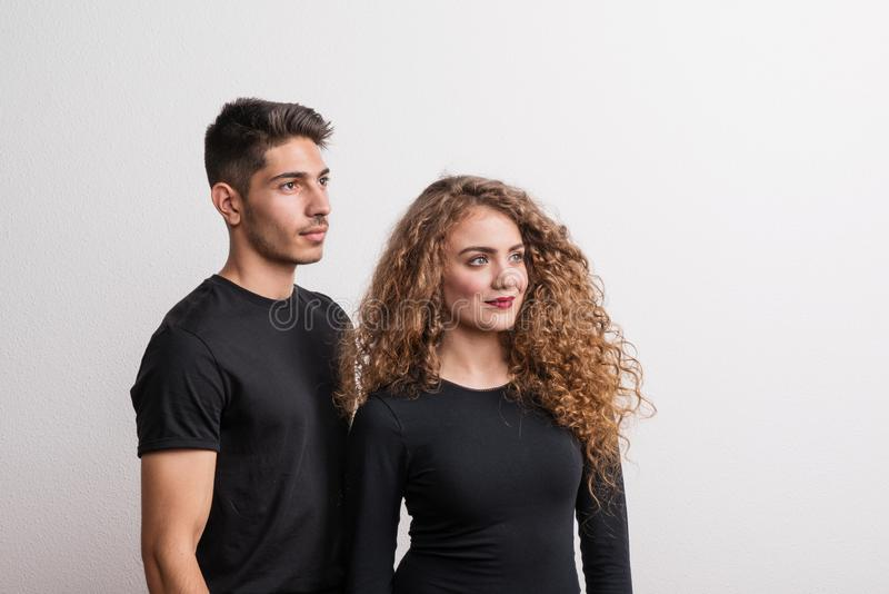 Το πορτρέτο μιας νεολαίας συνδέει τη στάση σε ένα στούντιο, που φορά τα μαύρα ενδύματα στοκ φωτογραφία με δικαίωμα ελεύθερης χρήσης