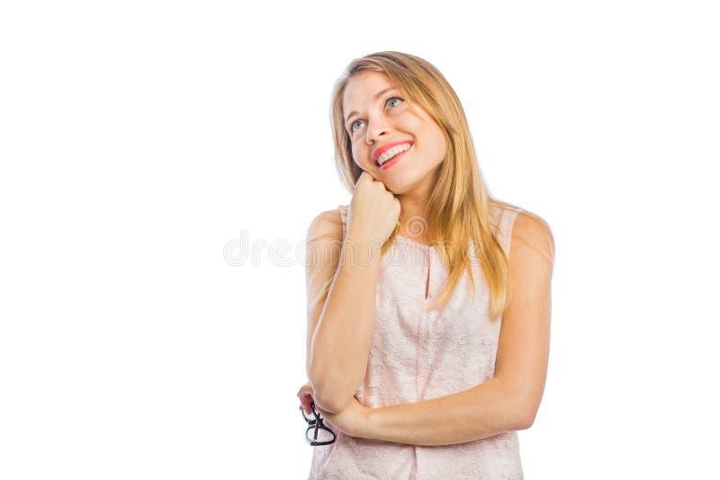 Το πορτρέτο μιας ονειροπόλου νέας γυναίκας με τα όπλα της δίπλωσε κάτω από το στήθος της κοιτάζοντας μακριά, μαγνητοσκόπηση σε έν στοκ φωτογραφία