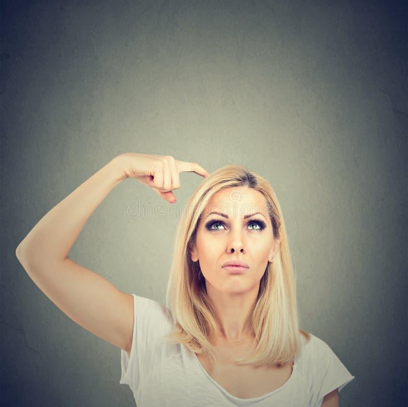 Το πορτρέτο μιας σκεπτόμενης γυναίκας που συγχέεται γρατσούνισμα του κεφαλιού της επιδιώκει μια λύση ανατρέχοντας στοκ εικόνες