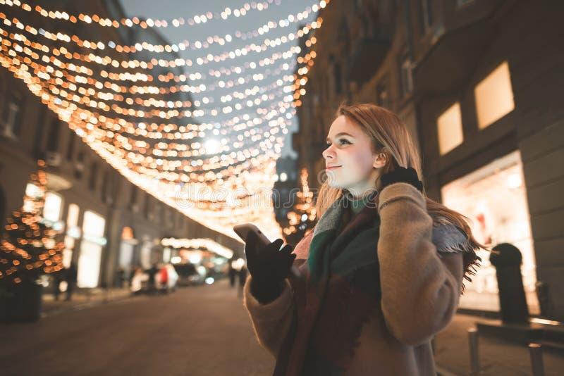 Το πορτρέτο μιας χαριτωμένης κυρίας στο θερμό ιματισμό χρησιμοποιεί ένα smartphone, κοιτάζει στην κατεύθυνση και χαμογελά σε έναν στοκ φωτογραφία