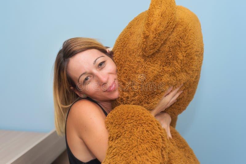 Το πορτρέτο μιας όμορφης γυναίκας που αγκαλιάζει το Teddy της αντέχει στοκ εικόνα με δικαίωμα ελεύθερης χρήσης