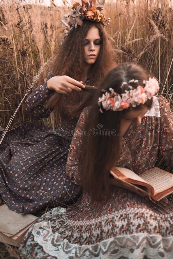 Το πορτρέτο μόδας δύο όμορφων κοριτσιών στον τομέα ηλιοβασιλέματος που φορά το boho όρισε τον ιματισμό στοκ εικόνα