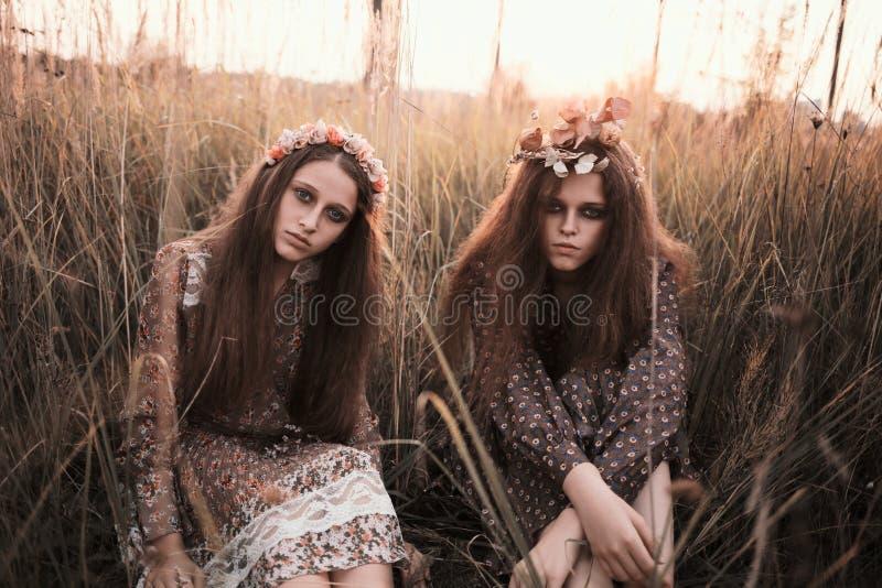 Το πορτρέτο μόδας δύο όμορφων κοριτσιών στον τομέα ηλιοβασιλέματος που φορά το boho όρισε τον ιματισμό στοκ εικόνες