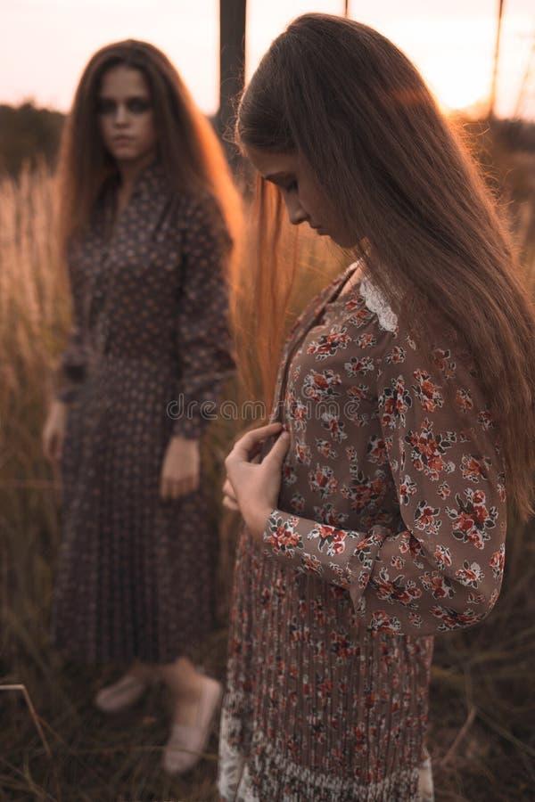 Το πορτρέτο μόδας δύο όμορφων κοριτσιών στον τομέα ηλιοβασιλέματος που φορά το boho όρισε τον ιματισμό στοκ φωτογραφία