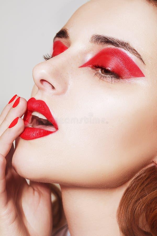 Το πορτρέτο ομορφιάς των προκλητικών γυναικών με τη γοητεία αποτελεί Κόκκινα χείλια και κόκκινες σκιές ματιών, neils Πρότυπο πρόσ στοκ φωτογραφίες με δικαίωμα ελεύθερης χρήσης