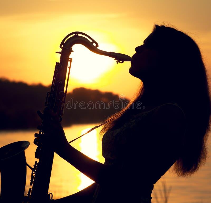 Το πορτρέτο σκιαγραφιών μιας νέας γυναίκας που skillfully που παίζει το saxophone στη φύση που δίνει την ειρήνη ηρεμίας της στοκ εικόνα