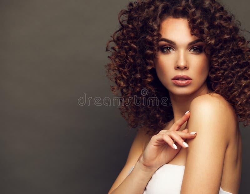 Το πορτρέτο στούντιο μόδας της όμορφης χαμογελώντας γυναίκας με το afro κατσαρώνει hairstyle Μόδα και ομορφιά στοκ εικόνες
