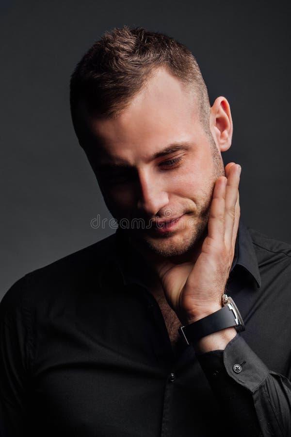 Το πορτρέτο στούντιο του νέου προκλητικού ατόμου στο μαύρο πουκάμισο, κράτημα παραδίδει το πηγούνι, κοιτάζοντας κάτω με την ταπει στοκ φωτογραφία