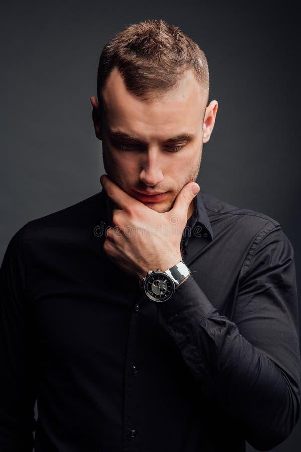 Το πορτρέτο στούντιο του νέου προκλητικού ατόμου στο μαύρο πουκάμισο, κράτημα παραδίδει το πηγούνι, κοιτάζοντας κάτω με την ταπει στοκ εικόνα με δικαίωμα ελεύθερης χρήσης