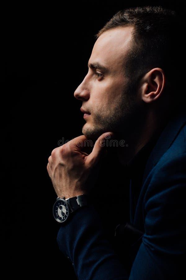 Το πορτρέτο στούντιο του νέου προκλητικού ατόμου στο μαύρο πουκάμισο, κράτημα παραδίδει το πηγούνι, κοιτάζοντας κάτω με την ταπει στοκ εικόνα