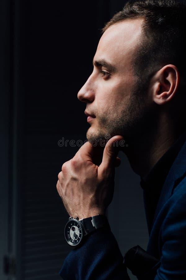 Το πορτρέτο στούντιο του νέου προκλητικού ατόμου στο μαύρο πουκάμισο, κράτημα παραδίδει το πηγούνι, κοιτάζοντας κάτω με την ταπει στοκ εικόνες