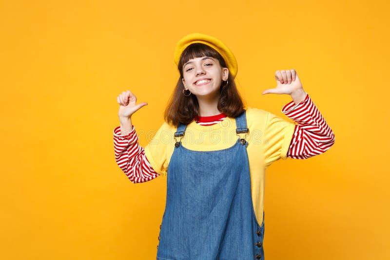 Το πορτρέτο της γοητείας του εφήβου κοριτσιών γαλλικό beret, τζιν sundress που δείχνει τους αντίχειρες σε την απομόνωσε σε κίτριν στοκ φωτογραφίες
