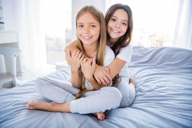 Το πορτρέτο της γοητευτικής τρίχας brunette παιδιών ξανθής έχει τα συναισθήματα που συνδέουν την υποστήριξη εμπιστοσύνης να καθίσ στοκ εικόνα