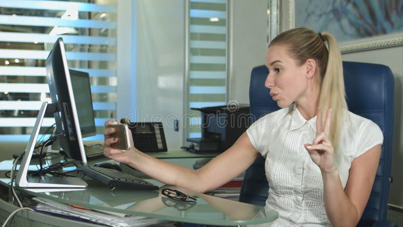 Το πορτρέτο της γυναίκας εργαζόμενος που παίρνει selfie απεικονίζει με τη χρησιμοποίηση ενός smartphone καθμένος στο γραφείο στοκ εικόνες με δικαίωμα ελεύθερης χρήσης