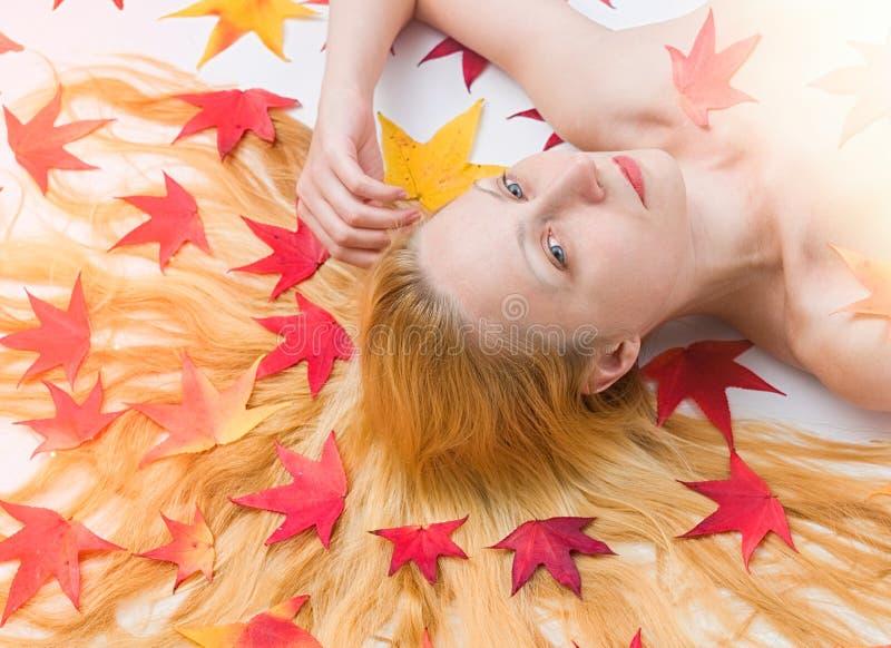 Το πορτρέτο της γυναίκας με το ζωηρόχρωμο φθινόπωρο βγάζει φύλλα στην τρίχα στοκ εικόνες