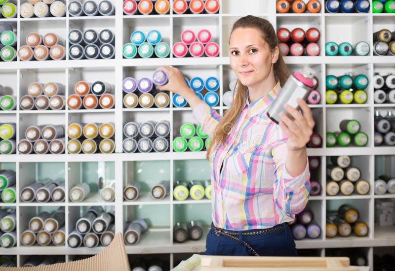 Το πορτρέτο της γυναίκας που επιλέγει το χρώμα χρωμάτων στο αερόλυμα μπορεί στην τέχνη SH στοκ φωτογραφίες