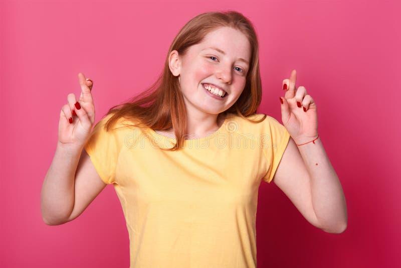 Το πορτρέτο της ελπίζουσας νέας γυναίκας στο περιστασιακό κίτρινο τ sirt, με την καφετιά τρίχα, που διασχίζει τα δάχτυλά της, ελπ στοκ εικόνες