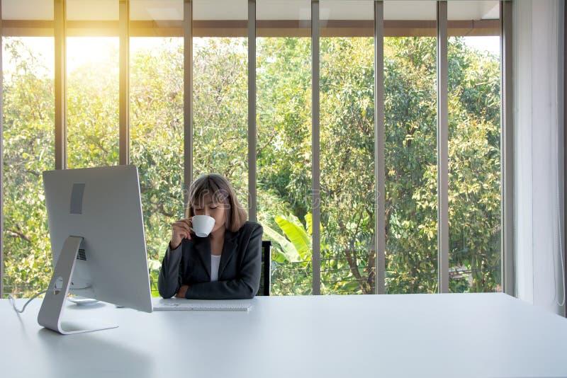 Το πορτρέτο της επιτυχούς χαλαρωμένης ονειροπόλου επιχειρησιακής κυρίας στηρίζεται στο χώρο εργασίας της και πίνει τον καφέ, μακρ στοκ εικόνες