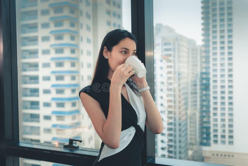 Το πορτρέτο της επιχειρηματία μιλά σε κάποιο στο κινητό τηλέφωνο και πίνει ένα φλιτζάνι του καφέ στεμένος ενάντια σε ένα παράθυρο στοκ φωτογραφία με δικαίωμα ελεύθερης χρήσης